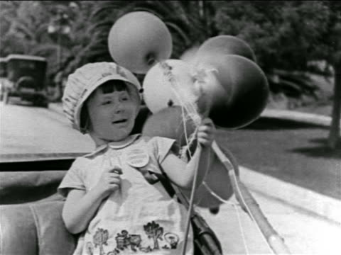 b/w 1927 little girl (baby peggy) sitting in backseat of car holding pinwheel / feature - seat stock videos & royalty-free footage