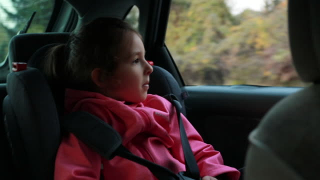 little girl sitting in car safety seat looking trough the window and trying to have a nap on a road trip - land vehicle stock videos & royalty-free footage