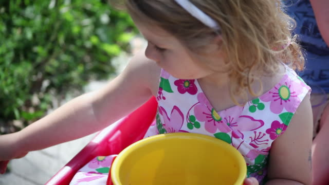 cu little girl sitting in wagon with her brother eating berries / toronto, ontario, canada - kelly mason videos video stock e b–roll