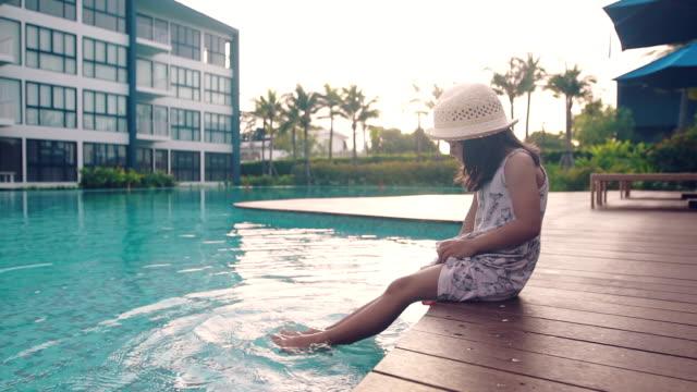 水で足でプールの端に座っている少女 - プールサイド点の映像素材/bロール