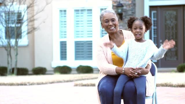 little girl sitting on her great grandmother's lap - davanti video stock e b–roll