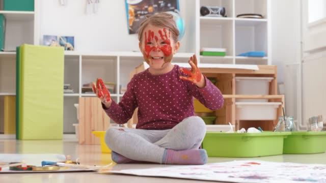 教室の床に座っている小さな女の子が彼女の目を横切って彼女の色の手を置く - レギンス点の映像素材/bロール