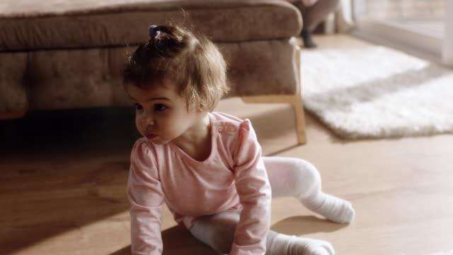 Little girl sitting on the floor at living room