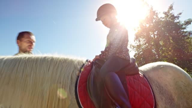 vídeos de stock, filmes e b-roll de uma menina sentada no cavalo da luz do sol - montar um animal