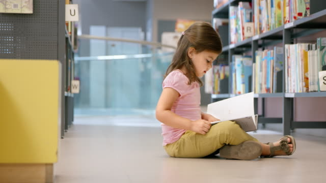 ds little girl sitting on the library's floor and reading - book stock videos & royalty-free footage