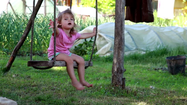 little girl sitting on the swings in the backyard - loneliness stock videos & royalty-free footage