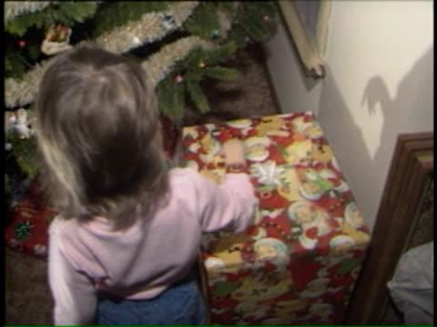 vídeos y material grabado en eventos de stock de little girl sitting under christmas tree on december 22, 1986 in chicago, illinois - regalo de navidad