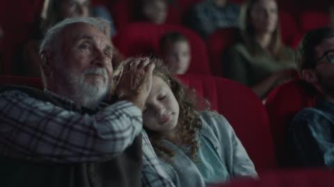 little girl sleeping on grandfather's shoulder in cinema - film screening stock videos & royalty-free footage