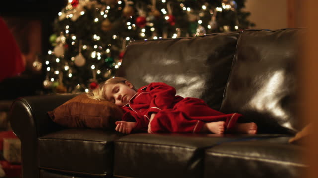 little girl sleeping on the couch while santa leaves presents - putting stock videos & royalty-free footage