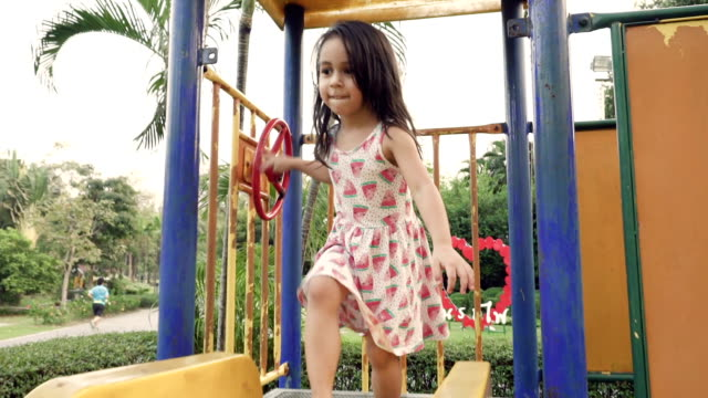 a little girl sliding down slide in park - parco giochi video stock e b–roll