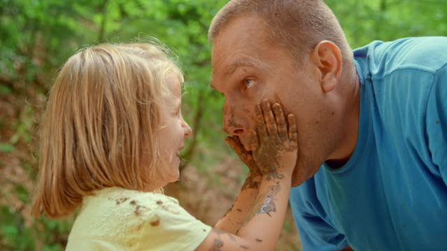 slo mo little girl smearing mud over her dad's face and laughing - face to face stock videos & royalty-free footage
