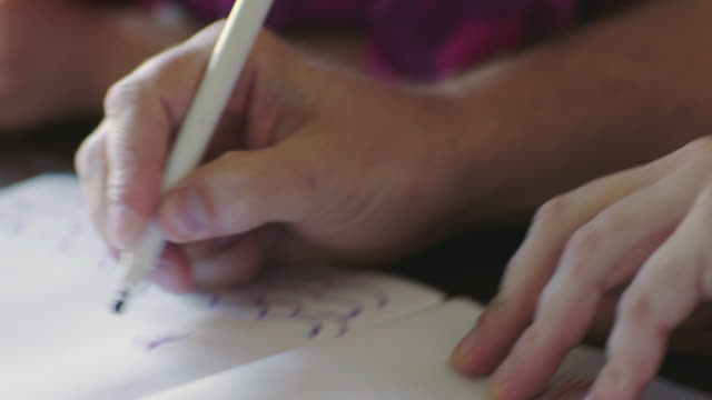 cu. little girl smiles and gives dad a kiss on the cheek as he draws a picture with magic marker. - homework stock videos & royalty-free footage