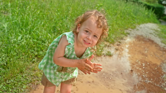 slo mo little girl smiling while dirtying her hands with mud and standing in the puddle with a stained top - macchiato video stock e b–roll