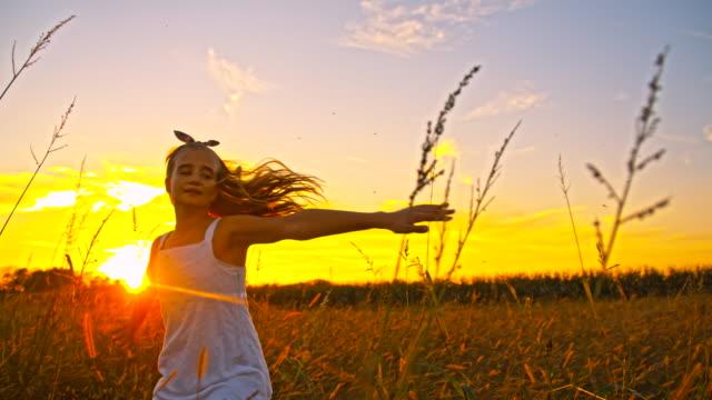 slo mo な少女スピニングの草地 - 10歳から11歳点の映像素材/bロール
