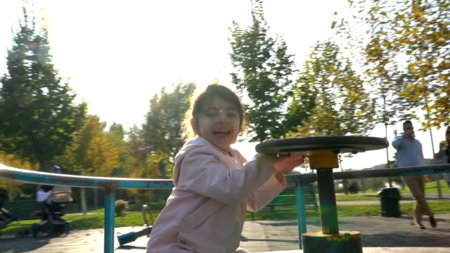 little girl spinning on playground - roundabout stock videos & royalty-free footage