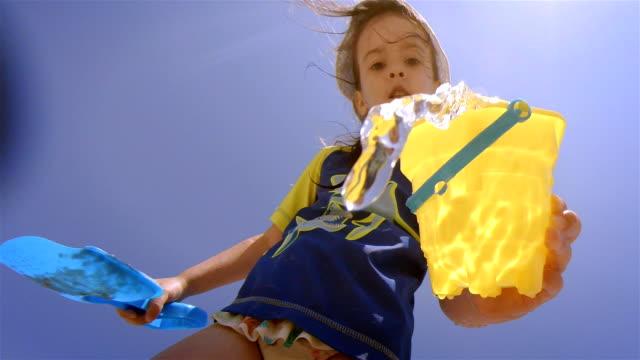 Little Girl Splashing Water At Camera While Having Fun At The Beach.