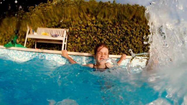 Little Girl Splashing Water At Camera While Having Fun At The Swimming Pool.