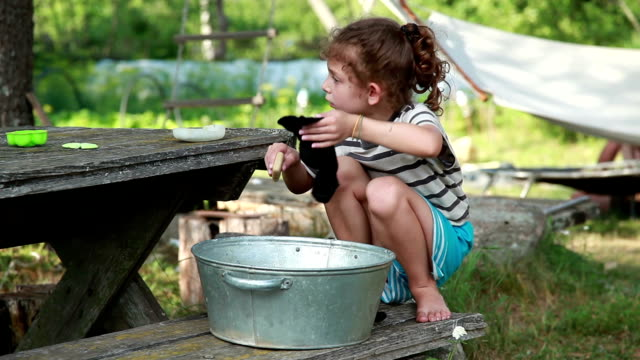 little girl squatting on the bench in front of the metal basin and rubbing dirty sock with a bar of soap - bar of soap stock videos & royalty-free footage