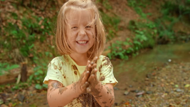 slo mo little girl standing in the forest creek and laughing covered in mud from head to toe - mud stock videos & royalty-free footage