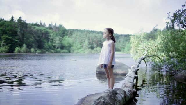 ms pan little girl standing up still on rock near lake / sidobre, midi-pyrennees, france - augen geschlossen stock-videos und b-roll-filmmaterial