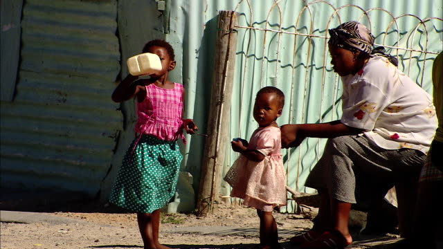 a little girl stands near her mother and sister and drinks from a plastic jug. - poor family stock videos & royalty-free footage