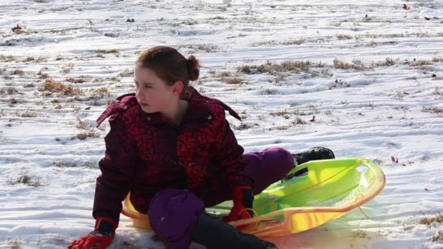 vidéos et rushes de little girl stops herself on her sled and then gets up to walk up the hill - kelly mason videos