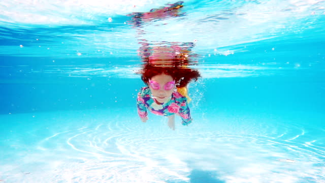 little girl swimming in pool blue water - moving down stock videos and b-roll footage