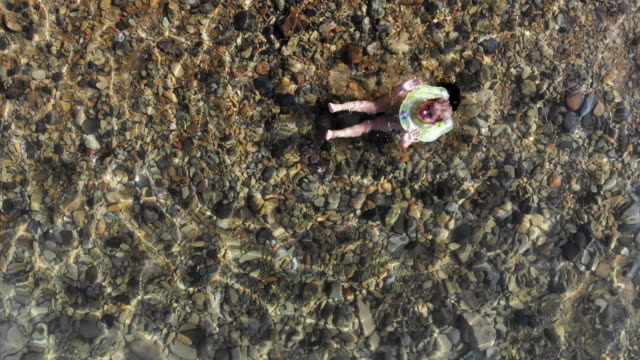 little girl swimming in the sea, aerial drone video - ozgurdonmaz stock videos and b-roll footage