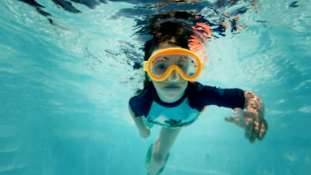 Little Girl Swimming Underwater in Swimming Pool