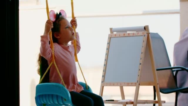 振り出しの近くのブランコでスイングする小さな女の子 - 製図板点の映像素材/bロール