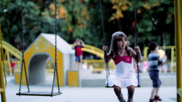 vídeos y material grabado en eventos de stock de little girl balanceo en un columpio - columpiarse