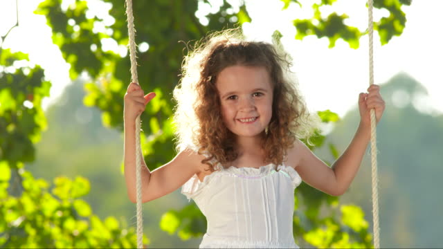 hd slow motion: little girl swinging on a tree swing - preschool student stock videos and b-roll footage