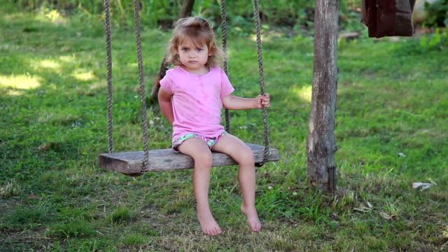 裏庭のブランコでスイングする小さな女の子 - 虫刺され点の映像素材/bロール