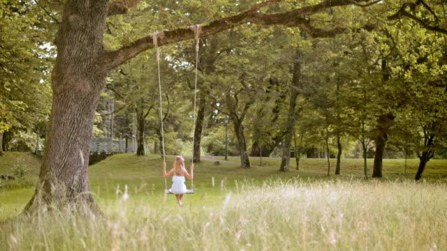 vídeos de stock e filmes b-roll de slo mo ds rapariga swing em uma árvore - vestido branco