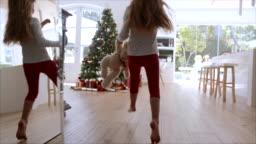 Little girl taking gift under Christmas tree