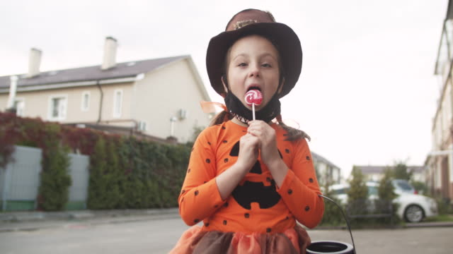 little girl taking off protective face mask and eating lollipop on halloween - lollipop stock videos & royalty-free footage