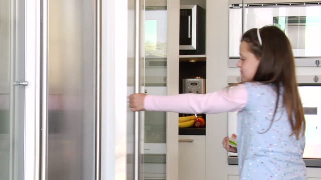 MS TS Little girl taking some fruits from fridge to her laptop in her kitchen / Los Angeles, California, United States