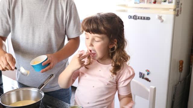 彼女のお父さんが鍋にバターを注いでいる間、小さな女の子は缶からコンデンスミルクの残り物を味わいます。 - dia点の映像素材/bロール