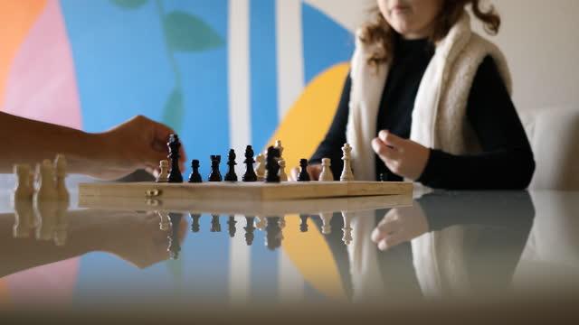 小さな女の子はチェスで彼女の作品を考え、動かす - dia点の映像素材/bロール