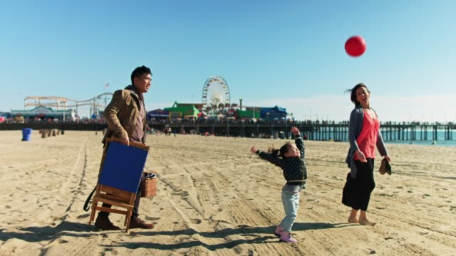 little girl throwing ball as family walks across santa monica beach - korean ethnicity stock videos & royalty-free footage