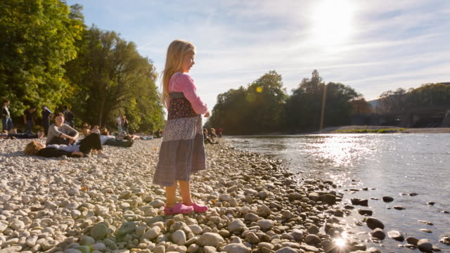 ms little girl throwing stones into river - baviera video stock e b–roll
