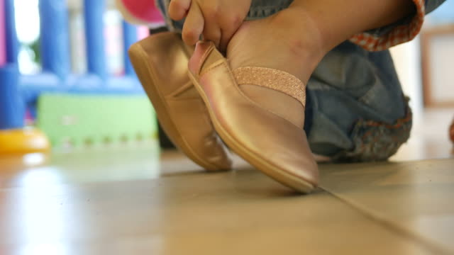 little girl trying on shoes with herself - shoelace stock videos and b-roll footage