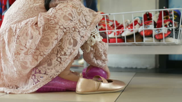 little girl trying on shoes with herself