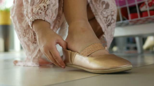 klein meisje probeert op schoenen met zichzelf