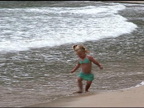 little girl turns circles on the beach. - endast flickor bildbanksvideor och videomaterial från bakom kulisserna