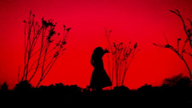 小さな女の子日没のシルエットで駆け巡って
