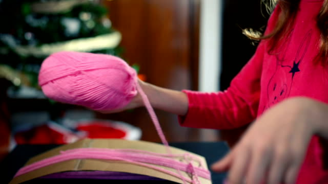little girl unwinding wool from a ball to use it in her artistic creation. - parte de una serie video stock e b–roll