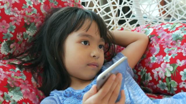 kleines mädchen verwendung webcam vom smartphone auf schaukel im wohnzimmer - little girl webcam stock-videos und b-roll-filmmaterial