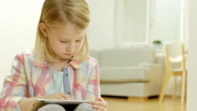 kleines mädchen mit einem tablet-pc zu hause - grundschulzeit stock-videos und b-roll-filmmaterial