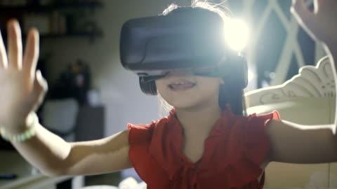 vídeos y material grabado en eventos de stock de niña usando unas gafas de realidad virtual en casa - simulador de realidad virtual